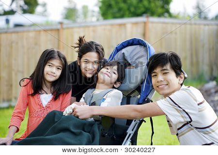 Three Children Surrounding A Small Disabled Child In Wheelchair