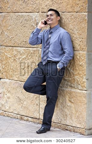 hispanische Kaufmann lehnend auf Steinmauer