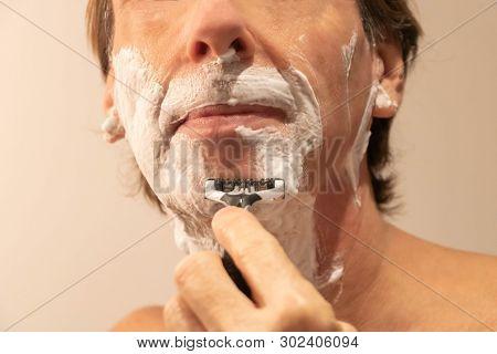 Man Shaving His Beard With A Manual Razor And Shaving Foam