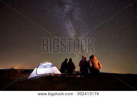 Back View Group Of Four Friends Tourists Sitting On A Bench Made Of Logs Together Around Campfire Be
