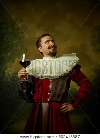 Young Man As A Medieval Knight On Dark Studio Background. Portrait Of Male Model In Retro Costume. H
