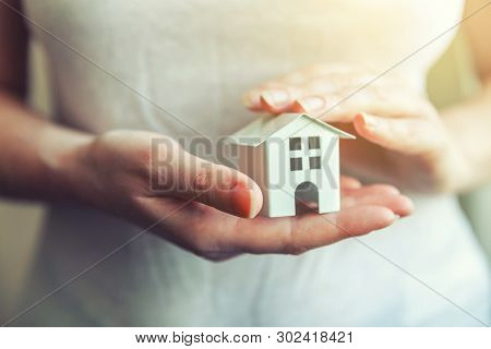 Female Woman Hands Holding Small Miniature White Toy House. Mortgage Property Insurance Dream Moving