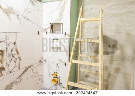 Bathroom Renovation Concept. Marble Ceramic Tiles With Spacers And Grey Cement Walls In Bathroom, Re
