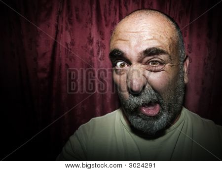 Man Making A Funny Face In Front Of Red Curtains