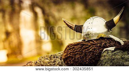 Equipment Of Viking Or Barbarian Warrior Outdoor On Nature. Viking Helmet On Brown Fur Of Animal In