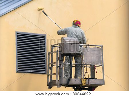Man On A Lifting Platform Painting The Building Wall With A Roller Exterior Outdoors. Worker On A La