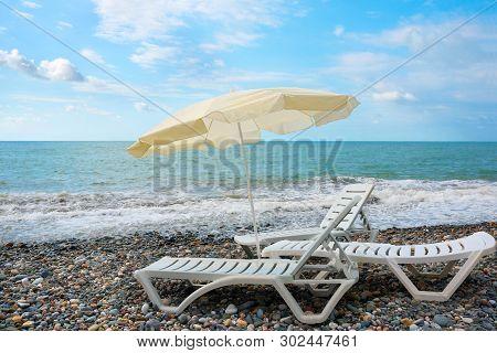 Deck-chairs And Beach Umbrella, Ashore Sea. Travel Background. Beach Chair On The Beach