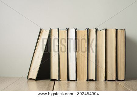 Row Of Old Books On Wooden Desk Back To School. Education Background.