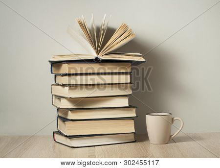 Open Book , Stack Of Old Books And Cup Of Coffee On Wooden Desk Back To School. Education Background