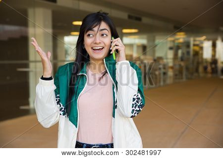 Medium Shot Of Pretty Young Mixed-race Woman In Green Jacket And Rose T-shirt Talking On Phone Outsi
