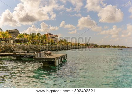 Pier With Diving Air Tanks Ready For Divers - View Back Onto Dive Resort - View From Calm Ocean Back