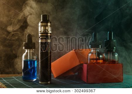 Electronic Cigarette And Bottles With Vape Liquids, Two Of Them Into Opened Gift Box, Surrounded By