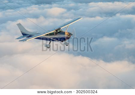 Stunning View Of A Blue And White Little Private Cessna Airplane Browsing The Sky Over Fluffy Fairy