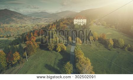 Carpathian High Mountain Hotel Aerial View. Colorful Highland Autumn Forest Panorama Overview. Hill Countryside Valley Nature Scenery. Travel, Tourism, Holidays, Relax. Drone Flight