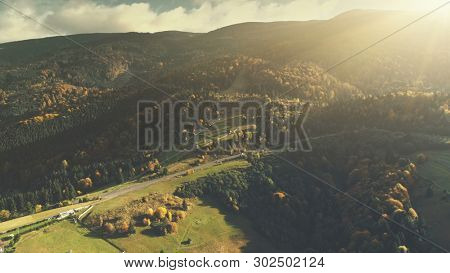 Mountain Valley Landscape Forest Slope Aerial View. Epic Wild Coniferous Wood Hill Countryside Road Overview. Soft Sunlight Panorama Scene Idyllic Village Travel Concept Drone Flight