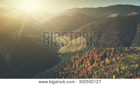 Epic Chain Hill Forest Slope Sun Beam Aerial View. Highland Village Dawn Sunlight Scenery Mountain Countryside Settlement. Homestead Cottage Sight Environment Concept Drone Flight