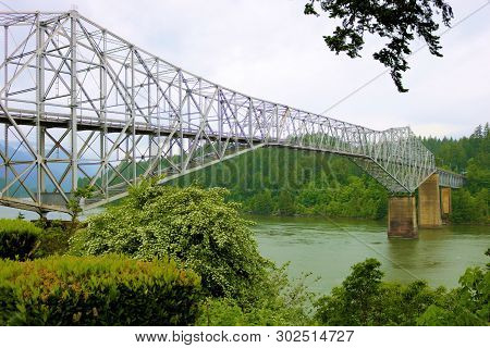 Historic Bridge With Large Trestles Over The Columbia River Surrounded By A Lush Temperate Forest Ta