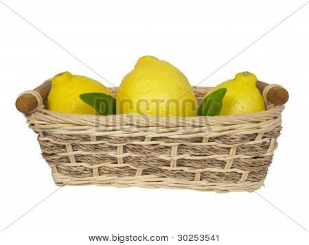 Three Yellow Lemons With Leaves In A Wattled Basket.