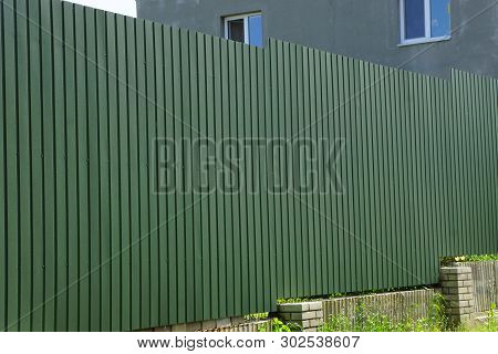 Long Private Green Metal Fence Outside In The Grass