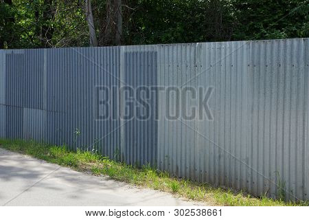 Long Private Gray Metal Fence Outside In The Grass