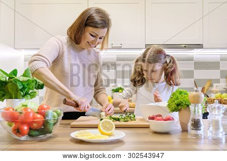 poster of Mother and child cooking together at home in kitchen. Healthy eating, mother teaches daughter to cook, parent child communication. Woman cutting eggs, girl cutting cucumbers for salad