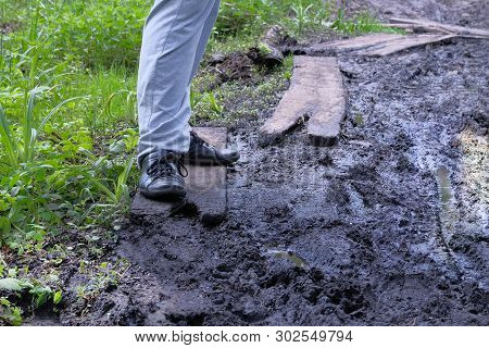 Dirty Country Road Wet Dirt, Impassibility. Mud And Puddles On The Dirt Road. Man Walk Along The For