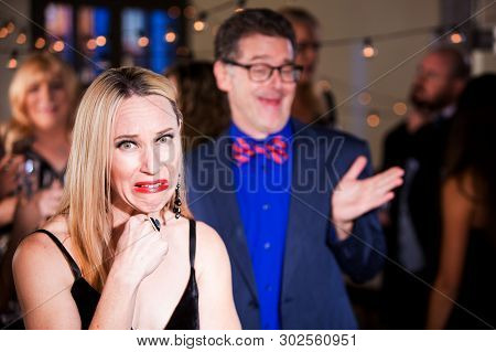 Woman Cringing With Boorish Man At Party