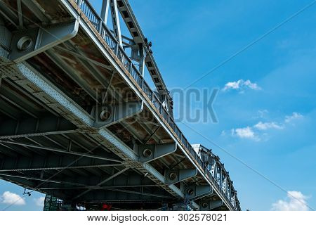 Steel Bridge Structure Against Blue Sky And White Clouds. Iron Bridge Engineering Construction. Stro