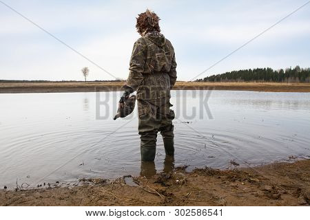 Duck Hunter With A Duck Decoy In His Hand Stands On The Shallow Water