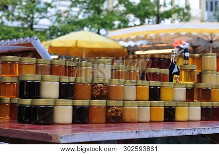 Glass Containers With Honey Stacked At Market Stall At Farmer´s Market