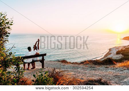 Happy Couple At Sunset. Man And Woman At Dawn. Couple Sitting On A Bench By The Sea. Couple In Love
