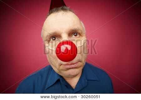 Portrait of unhappy man with a red nose celebrating all fools day