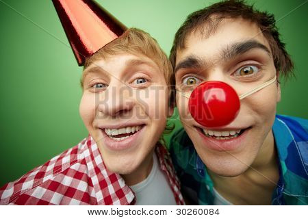 Two crazy guys making faces at camera on fool�s day, isolated on green background
