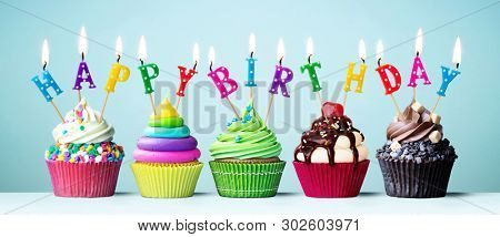 Colorful cupcakes with candles spelling Happy Birthday