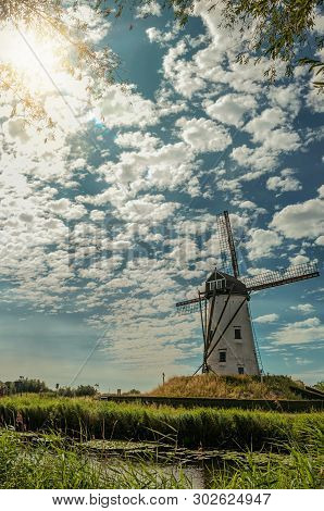 Old Windmill Next To Canal With Bushes And Grove, Sunlight And Blue Cloudy Sky, Near Damme. A Quiet