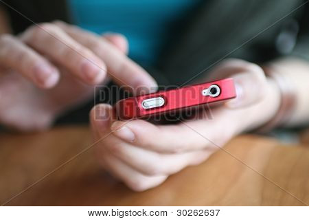 Young Woman's Hands Holding Red Smart Phone