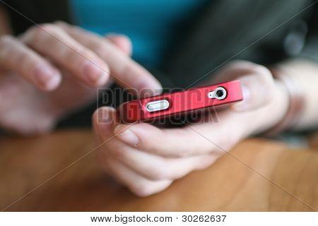 Mãos jovem mulher segurando o telefone inteligente vermelho