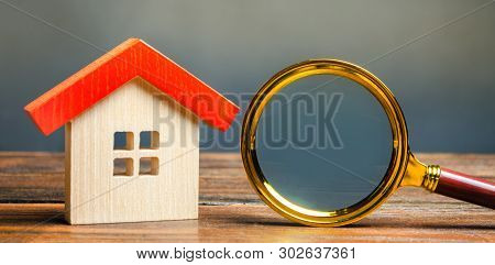 Miniature Wooden House And Magnifying Glass. Home Appraisal. Property Valuation. Choice Of Location
