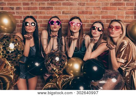 Portrait of nice cool company attractive alluring sweet fascinating winsome lovely lovable gorgeous cheerful cheery ladies having fun sending you kiss isolated over industrial brick wall. poster