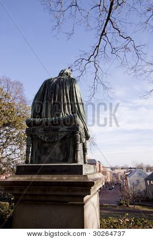 Bronze memorial statue of Roger Brooke Taney faces towards the city of Annapolis, MD from the grounds of the Maryland State House where the General Assembly convenes for three months a year.