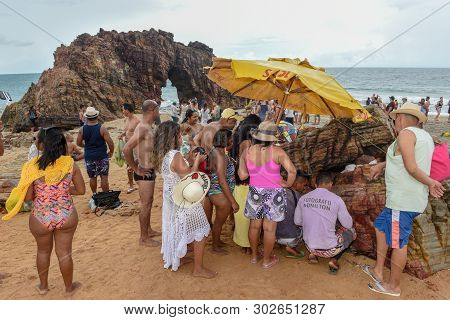 People Waiting For The Print Of The Souvenir Photo In Front Of The Natural Arch Of Jericoacoara On B