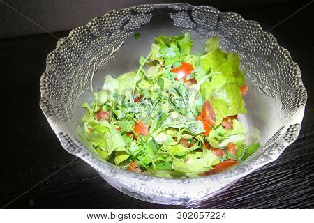Highlighted Glass Salad Bowl With Dark Background.
