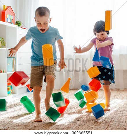 Little Brother And Sister Run Around The Room Spreading Legs Toy Raznocvetnye Plastikovye Blocks. Ch