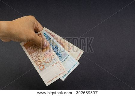 Hand Holding Fifty Croatian Kuna Or Sto Kuna Bank Notes On Black Background. Financial Concept And S