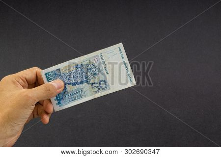 Hand holding fifty Croatian KUNA or STO KUNA bank notes on black background. Financial concept and selective focus poster