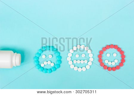 Multicolored Pills And Funny Faces And A Plastic Bottle On A Blue Background. The Concept Of Antidep