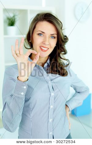 Young woman making an OK gesture and looking at camera