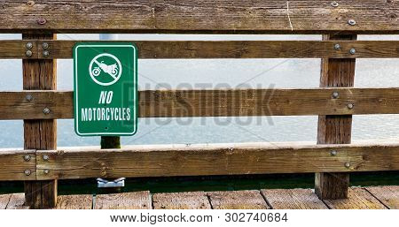 No Motorcycles Sign On A Wooden Rail Fence In Daylight