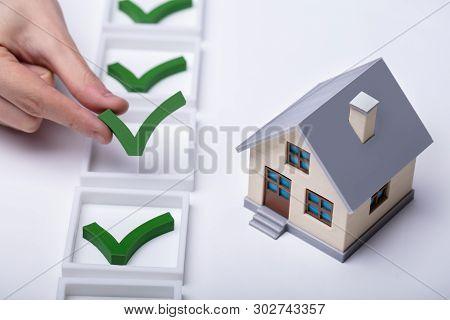 Check Mark Sign Near The House Model