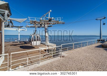 Lisbon, Portugal. Aerial Tramway leaving or entering terminal aka embarking or docking station, Parque das Nacoes aka Nations Park with Tagus River